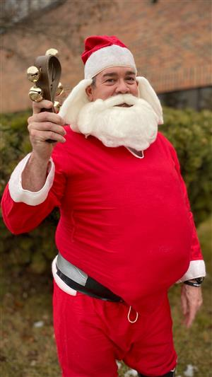North Central principal Steve Fisk is dressed in an old Santa Claus suit - complete with beard and hair - holding a bell.