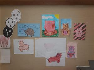 Student drawings of pigs in the Finch main office
