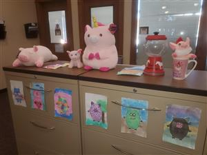 Pig stuffies line the cabinet at the Finch main office