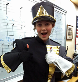 Female marching band student giving two big thumbs up and a smile